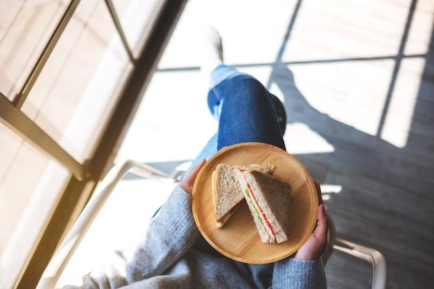 Imagem de vista superior de uma mulher segurando dois pedaços de sanduíche de trigo integral em uma placa de madeira enquanto está sentada na cadeira
