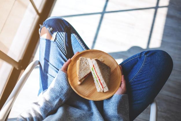 Imagem de vista superior de uma mulher segurando dois pedaços de sanduíche de trigo integral em uma placa de madeira enquanto está sentada no chão