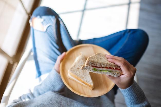 Imagem de vista superior de uma mulher segurando dois pedaços de sanduíche de trigo integral em uma placa de madeira