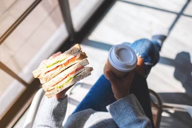 Imagem de vista superior de uma mulher segurando e comendo sanduíche de trigo integral e café pela manhã