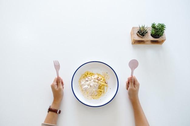 Imagem de vista superior de uma mulher segurando um garfo e uma colher, se preparando para comer espaguete carbonara na mesa