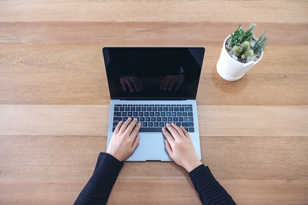 Imagem de vista superior de uma mulher usando e digitando no laptop com pote de cacto no fundo da mesa de madeira