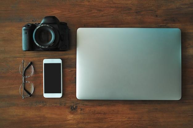 Imagem de vista superior do ambiente de trabalho em casa. freelance. sobre a mesa estão um laptop, um telefone, uma câmera profissional e óculos.