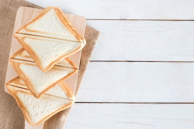 Imagem de vista superior do pão e pão fatiado na tábua na mesa de madeira branca, café da manhã na manhã, fresco caseiro, cópia espaço