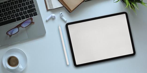 Imagem de vista superior do smartphone com tela em branco branca, colocando na mesa de trabalho branca e rodeado por computador portátil, vaso de plantas, caderno, diário, óculos, xícara de café, lápis e fone de ouvido sem fio.