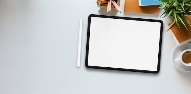 Imagem de vista superior do tablet computador com tela em branco branca, colocando na mesa de trabalho branca e rodeado por caneta, planta em vaso, caderno, diário, xícara de café, lápis e porta-lápis.