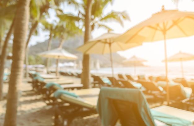 Imagem de vista traseira turva de espreguiçadeiras e guarda-chuva em uma praia tropical com árvores de coco
