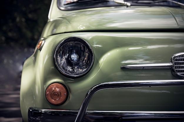 Imagem denominada retro de uma parte dianteira de um carro clássico verde.
