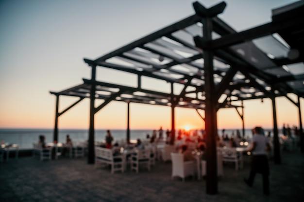 Imagem desfocada abstrata do terraço do restaurante ao ar livre na noite quente de verão, pôr do sol sobre o mar com