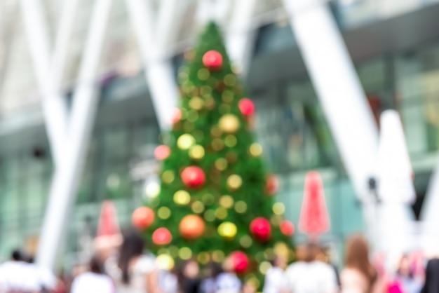 Imagem desfocada da árvore de natal decorada colorida ao ar livre com as pessoas