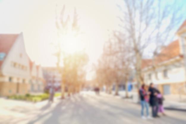 Imagem desfocada de pessoas caminhando ao longo da rua em uma aldeia.
