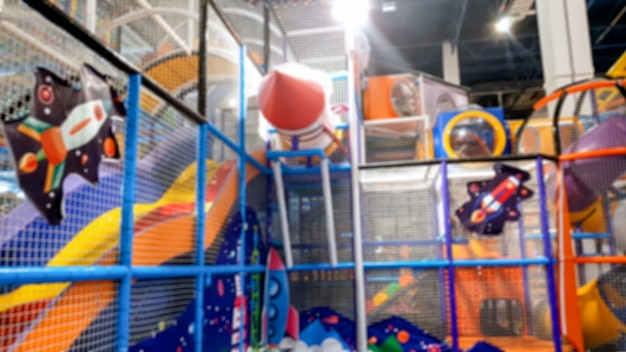 Imagem desfocada de um parque infantil colorido com muitos escorregas e escadas num parque de diversões num centro comercial