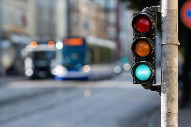 Imagem desfocada do tráfego da cidade com semáforos, em primeiro plano um semáforo com luz verde