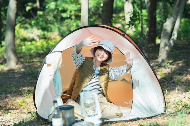 Imagem do acampamento solo - uma jovem acenando com um sorriso de dentro da tenda