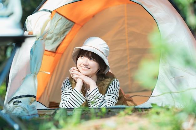 Imagem do acampamento solo - uma jovem deitada em uma tenda