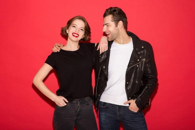 Imagem do alegre casal punk, abraçando e posando juntos sobre parede vermelha