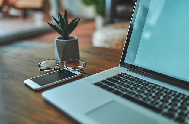 Imagem do ambiente de trabalho em casa. freelance. sobre a mesa está um laptop, um telefone e óculos.