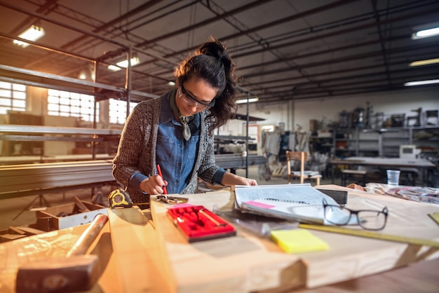 Imagem do arquiteto envelhecido médio focalizado bonito da mulher em sua oficina que trabalha em novos projetos.
