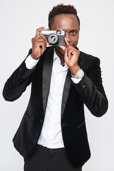 Imagem do atraente jovem empresário africano fazer uma foto com sua câmera. isolado sobre fundo branco.