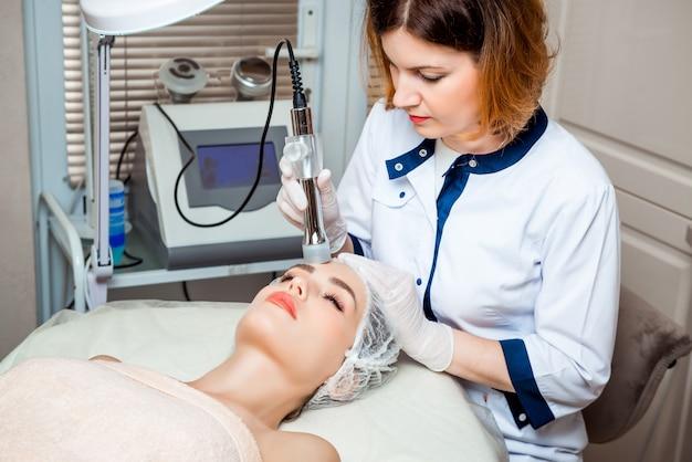 Imagem do belo esteticista fazendo oxigenoterapia para jovem mulher deitada