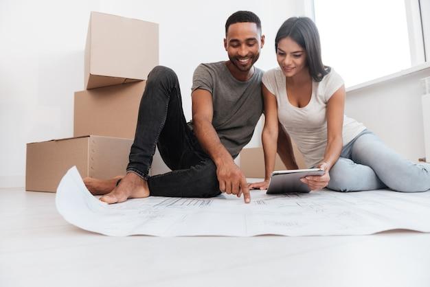 Imagem do casal planejando a decoração da nova casa, sentado no chão. festa de inauguração.