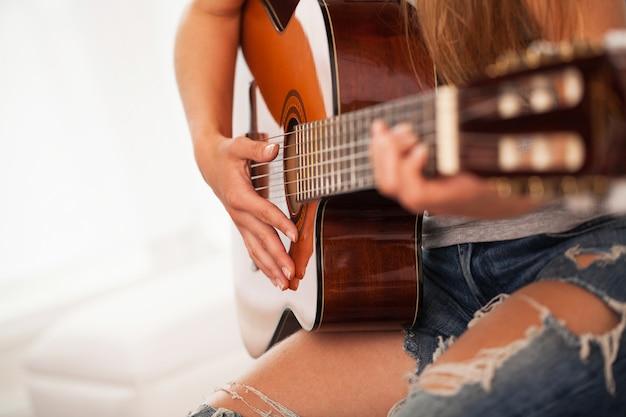 Imagem do close up da guitarra nas mãos da mulher