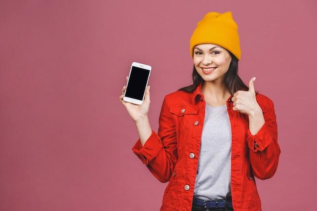 Imagem do close up da jovem mulher na tela de apresentação ocasional do copyspace do telefone móvel e que mostra o polegar isolado acima sobre a parede cor-de-rosa.