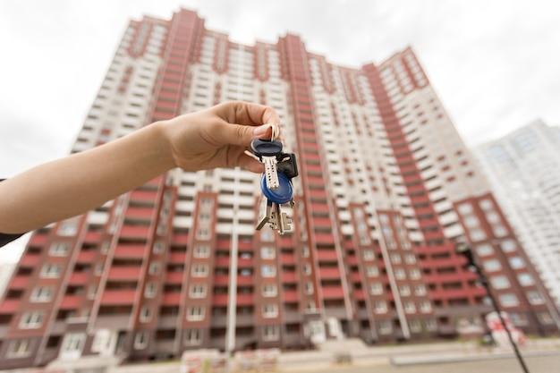 Imagem do close up da mão feminina segurando as chaves do apartamento novo.
