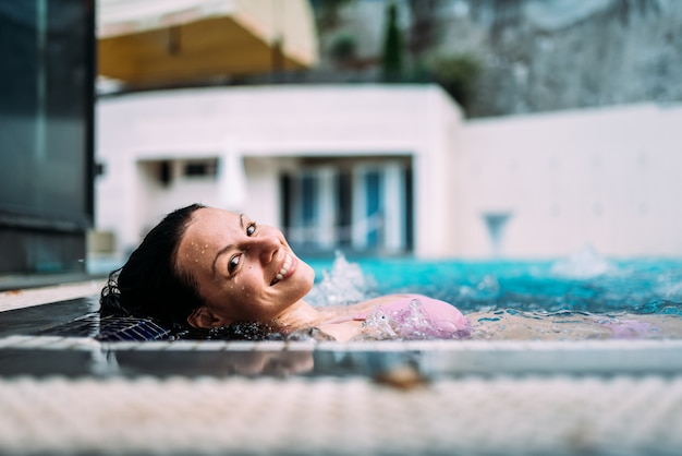 Imagem do close-up da mulher bonita que relaxa em uma banheira de hidromassagem fora.