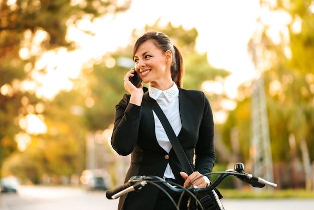 Imagem do close-up da mulher de negócios bonita que fala no telefone ao montar uma bicicleta.