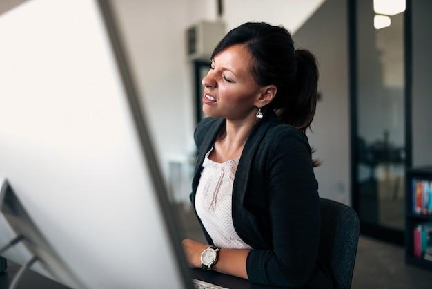 Imagem do close-up da mulher de negócios que tem o backpain.