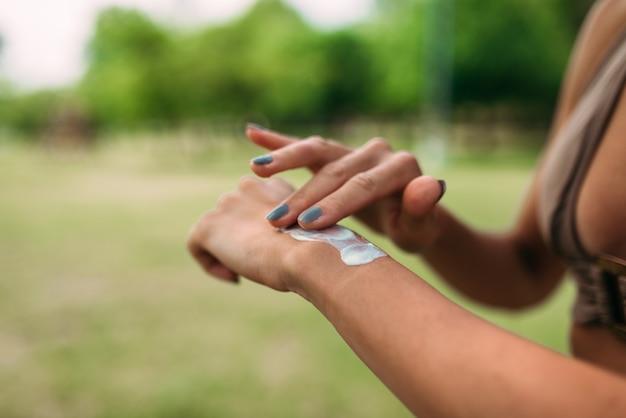 Imagem do close-up da pessoa fêmea irreconhecível que aplica a nata da proteção solar.