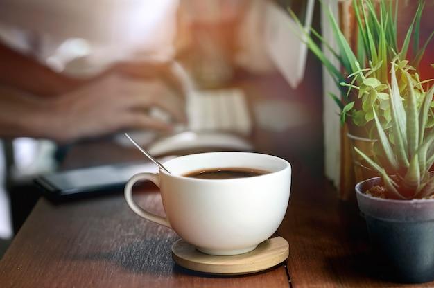 Imagem do close up da xícara de café branca no teable de madeira com imagem de borrão da mão que datilografa o teclado de computador