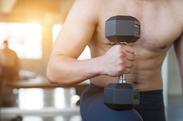 Imagem do close up de pesos de levantamento do homem na frente do fundo sujo da parede no gym velho.