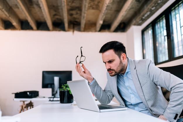 Imagem do close-up de um homem de negócio sério que guarda eyeglasess ao olhar a tela do portátil.