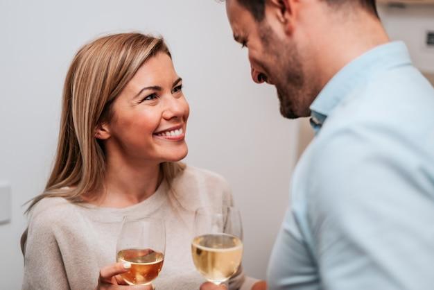 Imagem do close-up de um par que comemora com vinho branco.