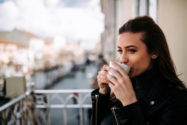 Imagem do close-up de uma menina bonita da mulher que come uma xícara de café no terraço.