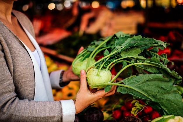 Imagem do close-up de uma mulher que guarda a couve-rábano no mercado.