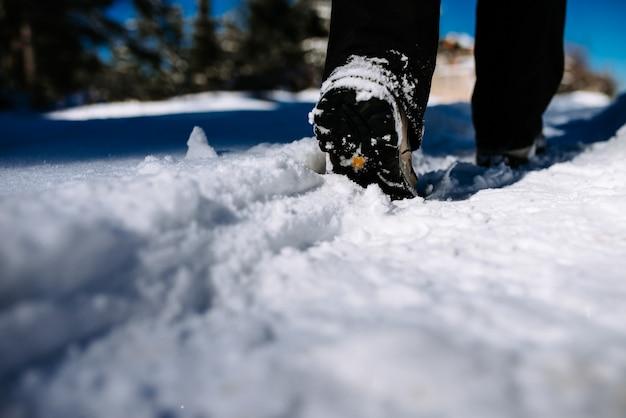 Imagem do close-up do caminhante que anda na montanha coberta com a neve.
