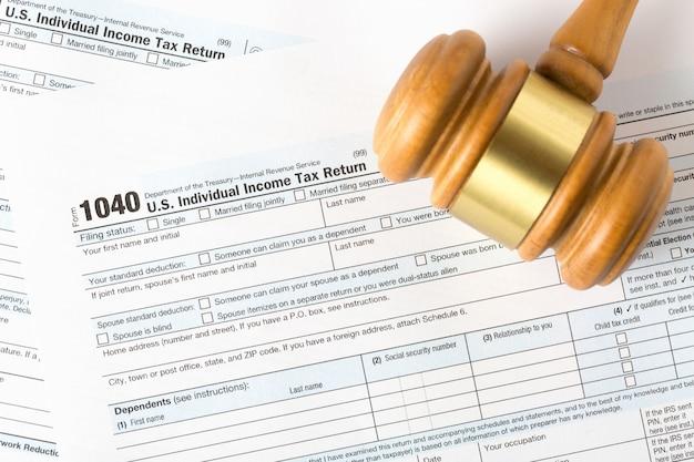 Imagem do close up do formulário de declaração de rendimentos individual americano 1040 com martelo do juiz.