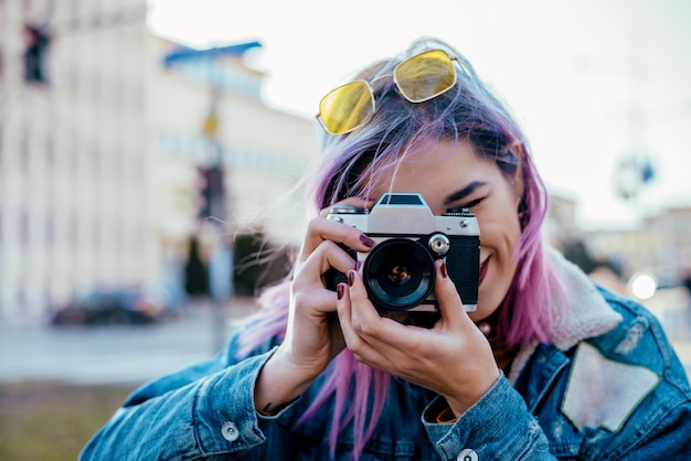 Imagem do close-up do fotógrafo fêmea urbano que usa a câmera.