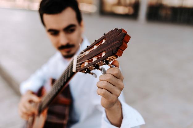 Imagem do close-up do homem novo que ajusta sua guitarra fora na cidade.