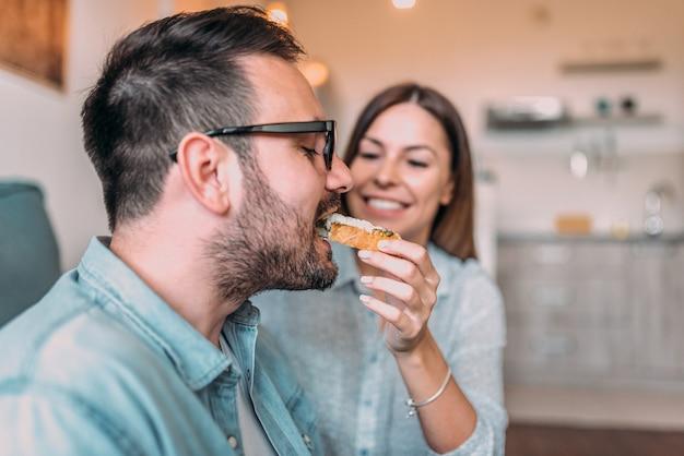 Imagem do close-up do marido que come o sanduíche da mão da sua esposa.