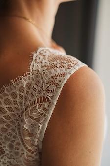 Imagem do close-up do ombro da noiva no vestido atado luxo. detalhes do casamento.