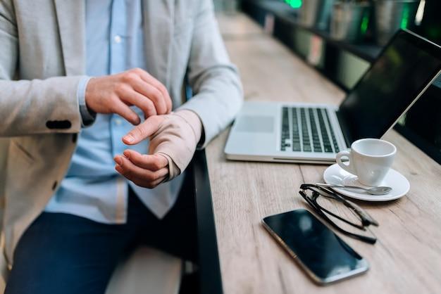 Imagem do close-up dos homens com a mão enfaixada que senta-se no café na frente de um laptop.