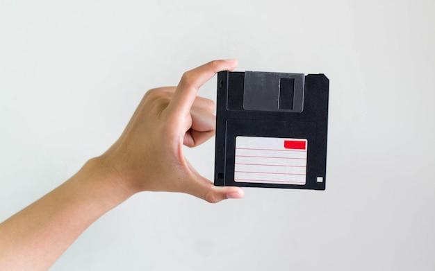 Imagem do close up: mão segurando o armazenamento de dados de disquete preto