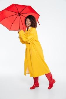 Imagem do comprimento total da mulher africana sorridente na capa de chuva