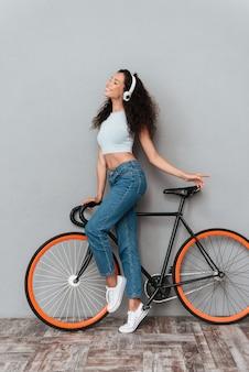 Imagem do comprimento total da mulher encaracolada sorridente em pé com bicicleta e ouvir música pelo fone de ouvido sobre fundo cinza