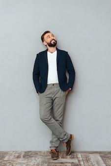 Imagem do comprimento total do homem barbudo sorridente em roupas de negócios, segurando os braços nos bolsos e olhando por cima do cinza