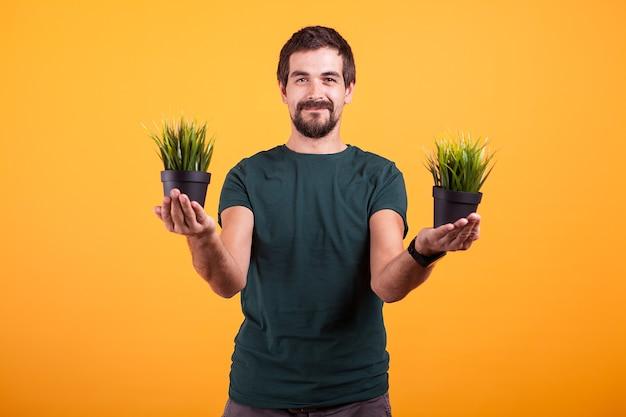 Imagem do conceito de tranquilidade de um homem relaxado segurando dois vasos de grama nas mãos